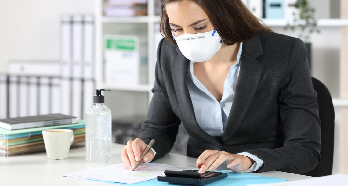 Woman working on finances wearing a protective mask